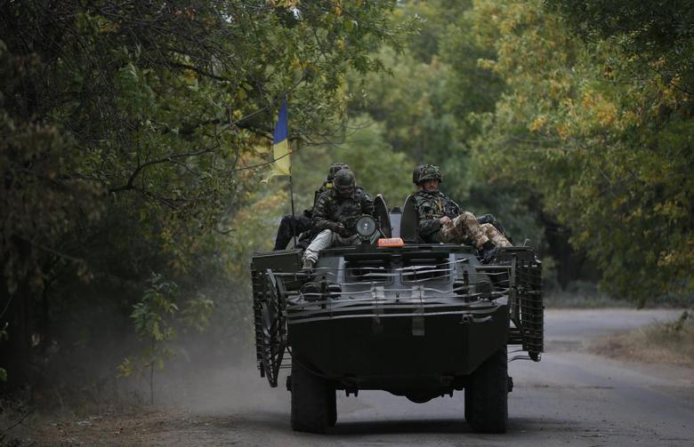 Ukrainian servicemen ride on an armoured vehicle near Kramatorsk, September 16, 2014. Russia threatened to send more troops to its newly-annexed territory of Crimea on Tuesday, after NATO began exercises in western Ukraine while Kiev's forces are fighting pro-Russian separatists in the east. REUTERS/David Mdzinarishvili (UKRAINE - Tags: POLITICS CIVIL UNREST MILITARY) - RTR46GKG