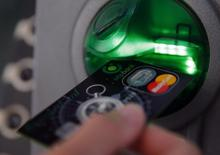 A customer performs a transaction on an ATM in a file photo.  REUTERS/Laszlo Balogh
