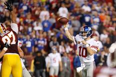 Sep 25, 2014; Landover, MD, USA; New York Giants quarterback Eli Manning (10) throws the ball over Washington Redskins defensive end Jason Hatcher (97) in the fourth quarter at FedEx Field. The Giants won 45-14. Mandatory Credit: Geoff Burke-USA TODAY Sports