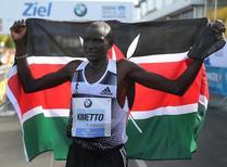 Dennis Kimetto of Kenya holds up his national flag as he celebrates winning the 41st Berlin marathon, September 28, 2014. REUTERS/Hannibal Hanschke
