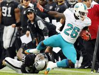 Miami Dolphins' Lamar Miller (R) is tackled by Oakland Raiders' Kaluka Maiava during the first half of their NFL football game at Wembley Stadium in London, September 28, 2014.  REUTERS/Suzanne Plunkett