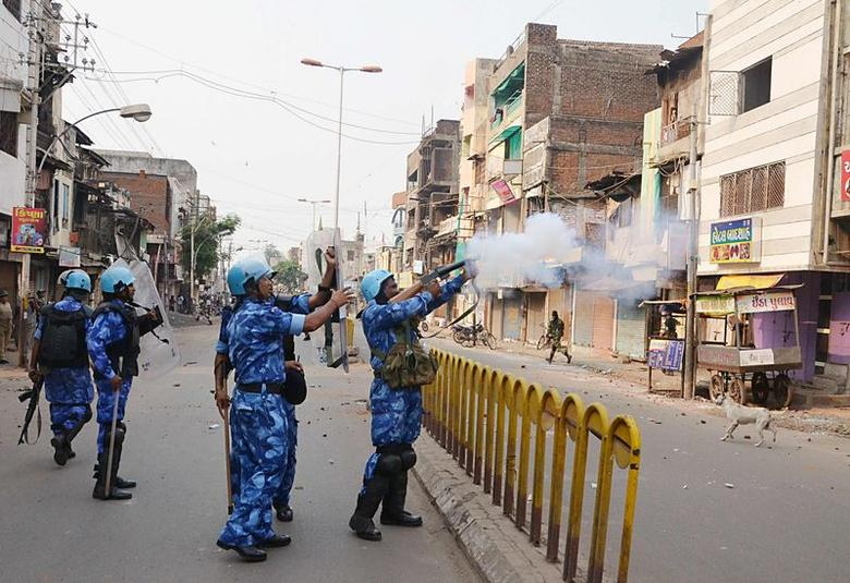 A Rapid Action Force (RAF) member fires a tear gas shell to disperse a mob after clashes in Vadodara in the western Indian state of Gujarat September 26, 2014. REUTERS/Stringer