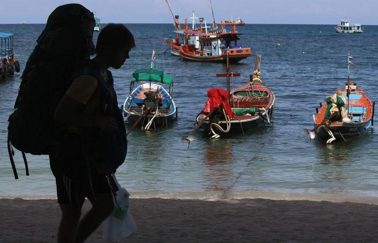 A tourist carries his backpack after arriving at Koh Tao Island (Turtle Island) September 21, 2014. REUTERS/Chaiwat Subprasom