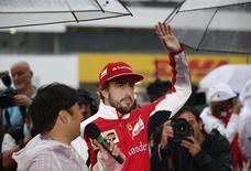 Ferrari Formula One driver Fernando Alonso of Spain greets fans at the Suzuka circuit in Suzuka, western Japan, October 2, 2014, ahead of Sunday's Japanese F1 Grand Prix. REUTERS/Toru Hanai
