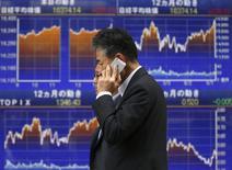 Un hombre pasa frente una pantalla que muestra el índice Nikkei en Tokio. Imagen de archivo, 25 agosto, 2014. Las bolsas de Asia se estabilizaban el viernes luego de que las acciones de Hong Kong rebotaron de mínimos en varios meses, pero aún se encaminan a una cuarta semana consecutiva de pérdidas en medio de las preocupaciones sobre el crecimiento global. REUTERS/Toru Hanai