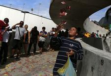 Menino joga panfletos enquanto moradores da Rocinha esperam para votar no Rio de Janeiro.  5/10/2014 REUTERS/Pilar Olivares