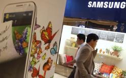 Люди в магазине Samsung Electronics в Сеуле 22 октября 2012 года. Samsung Electronics Co Ltd планирует построить новый завод по производству чипов в Южной Корее за $14,7 миллиарда, пытаясь сосредоточиться на производстве полупроводников при падении прибыли от продажи мобильных телефонов. REUTERS/Kim Hong-Ji