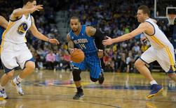 Mar 18, 2014; Oakland, CA, USA; Orlando Magic guard Jameer Nelson (14) drives in between Golden State Warriors guard Klay Thompson (11) and forward David Lee (10) during the second quarter at Oracle Arena. Mandatory Credit: Kelley L Cox-USA TODAY Sports