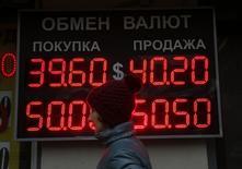 Женщина проходит мимо вывески пуьнкта обмена валюты в Москве 6 октября 2014 года. Рубль утром вторника торгуется с минимальными изменениями в русле утренних тенденций форекса и после частичного насыщения локального спроса на валюту путем её покупки у Центробанка в предыдущие две биржевые сессии, а также после падения накануне к историческим минимумам. REUTERS/Maxim Shemetov
