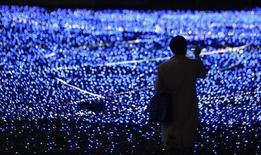 Мужчина фотографирует рождественскую декорацию из светодиодов в Токио 20 ноября 2009 года. Нобелевскую премию по физике 2014 года получили ученые Исаму Акасаки, Хироси Амано из Японии и американец японского происхождения Сюдзи Накамура за изобретение светодиодов. REUTERS/Toru Hanai