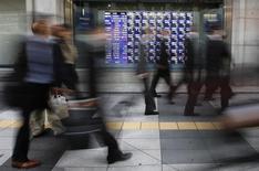 Personas caminan frente a una pizarra eléctrica que muestra índices económicos en Tokio. Imagen de archivo, 04 diciembre, 2013.  Las bolsas de Asia subían el martes y el dólar languidecía después de que los inversores recogieron algunas ganancias de su repunte reciente. REUTERS/Toru Hanai