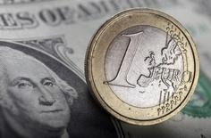 Долларовая купюра и монета в один евро в Варшаве 26 января 2011 года. Курс евро к доллару упадет до $0,95 к 2017 году, опустив единую европейскую валюту ниже паритета впервые более чем за 10 лет, говорится в докладе Deutsche Bank. REUTERS/Kacper Pempel