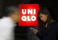 Женщина проходит мимо магазина Uniqlo в Токио 7 октября 2014 года. Японский ритейлер Fast Retailing Co ждет роста прибыли на 38 процентов в текущем финансовом году благодаря расширению линейки продуктов под брендом Uniqlo, сообщила компания. REUTERS/Yuya Shino