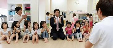 Japan's Prime Minister Shinzo Abe (C) plays with children as he inspects a daycare center in Yokohama, south of Tokyo, in this photo distributed by Kyodo May 21, 2013.  REUTERS/Kyodo