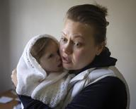 Viktoria holds her daughter Stephanya, aged one year and three months, at a clinic which specialises in children's neurological disorders in Donetsk, eastern Ukraine, October 10, 2014. REUTERS/Shamil Zhumatov