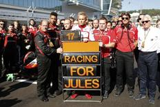 Marussia Formula One driver Max Chilton of Britain (C) and his team members pray for Marussia Formula One driver Jules Bianchi of France who had an accident in the previous race, before the first Russian Grand Prix in Sochi October 12, 2014. REUTERS/Pool/Valdrin Xhemaj