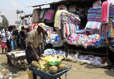 A vender sells pineapples next to a second hand stall at the Gikomba market in Nairobi September 18, 2014. REUTERS/Noor Khamis