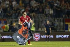 Stefan Mitrovic of Serbia grabs a flag depicting so-called Greater Albania, an area covering all parts of the Balkans where ethnic Albanians live, that was flown over the pitch during their Euro 2016 Group I qualifying soccer match against Albania at the FK Partizan stadium in Belgrade October 14, 2014. REUTERS/Marko Djurica