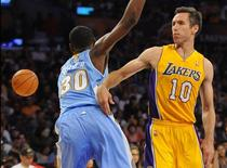 Los Angeles Lakers guard Steve Nash (10) passes the ball away from Denver Nuggets forward Quincy Miller (30) during the first half at Staples Center. Mandatory Credit: Christopher Hanewinckel-USA TODAY Sports
