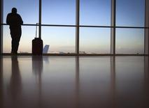 A passenger looks out the window at Miami International Airport in Miami December 10, 2013.  Picture taken December 10, 2013.     REUTERS/Carlo Allegri
