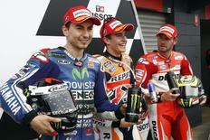 Repsol Honda MotoGP rider Marc Marquez (C) of Spain, Yamaha MotoGP's Jorge Lorenzo (L) of Spain and Ducati's Cal Crutchlow of Britain are pictured after qualifying for the Australian Grand Prix on Phillip Island October 18, 2014. REUTERS/Jason Reed