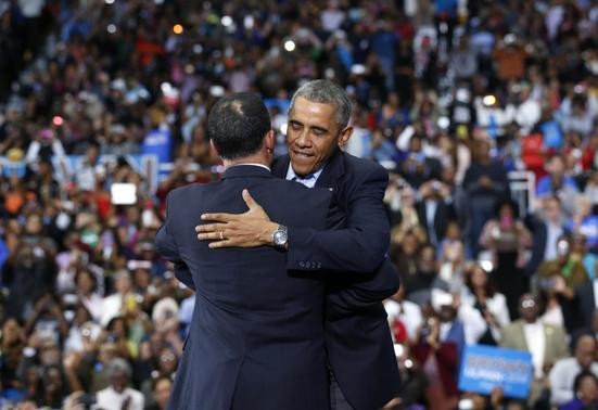 U.S. President Barack Obama hugs Maryland Lt. Gov. Anthony Brown at a campaign rally for Brown at a High School in Upper Marlboro, Maryland October 19, 2014. REUTERS-Kevin Lamarque