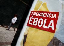 Плакат с призывом пожертвований на борьбу с вирусом Эбола на автобусной остановке в Мадриде 8 октября 2014 года. Всемирная организация здравоохранения (ВОЗ) при ООН в понедельник объявила Нигерию свободной от вируса Эбола, поскольку за шесть недель здесь не было зарегистрировано новых случаев смертоносной лихорадки - достижение, призванное стать примером для стран, пытающихся обуздать опасное заболевание. REUTERS/Sergio Perez