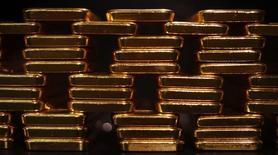 Imagen de archivo de unas barras de oro almacenadas en la planta de la firma ProAurum en Múnich, mar 6 2014. Los precios de oro quedarían rezagados respecto a metales preciosos de uso industrial como el platino y el paladio en el 2015, según un sondeo de Reuters entre analistas, en momentos en que la gradual estabilización de la economía mundial favorece a materias primas por sobre los llamados activos de refugio.   REUTERS/Michael Dalder