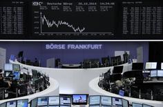 Traders are pictured at their desks in front of the DAX board at the Frankfurt stock exchange October 20, 2014.     REUTERS/Remote/Stringer