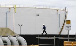 Un trabajador pasa al lado de un reserva de petróleo en la refinería Caltex de Sydney en Kurnell. Imagen de archivo, 14 octubre, 2014.  La Organización de Países Exportadores de Petróleo debería recortar su producción diaria de crudo en al menos 500.000 barriles por día (bpd), dijo un funcionario petrolero libio, para enfrentar el sobreabastecimiento y respaldar a los precios, que han caído a mínimos de cuatro años. REUTERS/Jason Reed