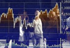 Personas se ven reflejadas en una pantalla electrónica que muestra gráficos de las fluctuacioens de la bolsa de Tokio, en Tokio. Imagen de archivo, 17 octubre, 2014. Las bolsas de Asia se hundían el jueves después de que un retroceso en Wall Street y una caída en los precios del crudo reavivó la inquietud de los inversores sobre la desaceleración del crecimiento global, mientras que una imagen dispar de la manufactura china no logró impresionar a los mercados. REUTERS/Yuya Shino