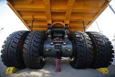 """Una visitante observa detalles de un camión minero durante la feria de la industria""""Expomin 2014"""", en Santiago, abr 21 2014. La inversión extranjera directa en América Latina cayó un 23 por ciento en el primer semestre por la ausencia de grandes adquisiciones y el enfriamiento de las inversiones en minería, dijo el jueves la Comisión Económica para América Latina y el Caribe (CEPAL). REUTERS/Ivan Alvarado"""