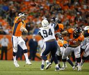 Denver Broncos quarterback Peyton Manning (18) throws a pass over San Diego Chargers defensive end Corey Liuget (94) during the first half at Sports Authority Field at Mile High. Chris Humphreys-USA TODAY Sports