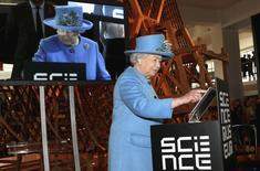 La reina Isabel II de Inglaterra aprieta un botón para enviar su primer tuit en la apertura de una nueva galería en el Museo de Ciencias de Londres, 24 octubre, 2014.  La reina Isabel II de Inglaterra hizo su primera incursión en el mundo de los medios sociales el viernes con un mensaje en su cuenta en Twitter. REUTERS/Chris Jackson/Pool