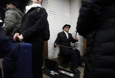 A man plays an erhu, a traditional Chinese instrument, in the subway following the 14th annual Chinatown Lunar New Year Parade in New York, in this February 17, 2013 file photo.  REUTERS/Carlo Allegri/Files