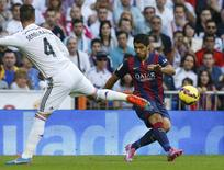 """Barcelona's Luis Suarez (R) kicks the ball past Real Madrid's Sergio Ramos during their Spanish first division """"Clasico"""" soccer match at the Santiago Bernabeu stadium in Madrid October 25, 2014.       REUTERS/Sergio Perez"""