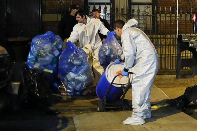 Members of a cleaning crew with ''Bio Recovery Corporation'' wearing personal protective equipment (PPE) push a barrel to be loaded in a truck of Centers for Disease Control and Prevention (CDC) after cleaning the apartment where Dr. Craig Spencer lives in New York October 24, 2014. REUTERS/Eduardo Munoz