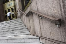 Standard Chartered a vu son bénéfice d'exploitation reculer de 16% au troisième trimestre à 1,5 milliard de dollars (1,18 milliard d'euros) et s'attend à une nouvelle baisse de ses bénéfices sur les trois derniers mois de l'année en raison d'une augmentation des créances douteuses et des coûts liés à l'évolution de la réglementation. /Photo prise le 6 août 2014/REUTERS/Tyrone Siu