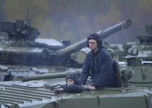 Премьер-министр Украины Арсений Яценюк (справа) на бронемашине в Яворове, к западу от Львова 21 октября 2014 года. Премьер Украины Арсений Яценюк предложил всем партиям, прошедшим в новый парламент, кроме Оппозиционного блока, в течение трех недель сформировать широкую проевропейскую коалицию и правительство, во главе которого в этом случае останется он сам. REUTERS/Andrew Kravchenko/Pool