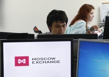Сотрудники Московской биржи за работой 3 июня 2014 года. Российский индекс ММВБ начал торги четверга с легкого повышения, сохраняя положительную динамику пятую сессию подряд, а долларовый индекс РТС скорректировался. REUTERS/Sergei Karpukhin