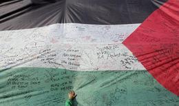 Палестинский флаг во время попытки установить рекорд Книги Гиннесса в Рамалле 28 октября 2014 года. Швеция первой из крупнейших европейских стран официально признает в четверг государством Палестинскую автономию, сообщила министр иностранных дел Швеции Маргот Вальстром. REUTERS/Ammar Awad