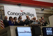 ConocoPhillips Chairman and Chief Executive Officer Ryan M. Lance (C) rings the closing bell at the New York Stock Exchange (NYSE), February 27, 2013.   REUTERS/Brendan McDermid
