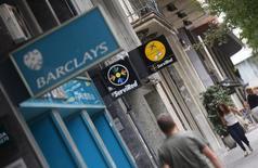 Personas pasan frente a una oficina de Barclays en Barcelona. Imagen de archivo, 1 septiembre, 2014. Barclays ha reservado 500 millones de libras esterlinas (634 millones de euros) para cubrir posibles multas por la manipulación de los mercados de divisas, lo que restó algo de brillo a un aumento de sus beneficios en el tercer trimestre gracias a una reducción de costes. REUTERS/Albert Gea