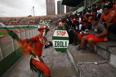 A fan of Ivory coast holds a sign with a message against Ebola during the 2015 African Nations Cup qualifying soccer match between Ivory Coast and Sierra Leone at the Felix Houphouet Boigny stadium in Abidjan September 6, 2014.  REUTERS/Luc Gnago