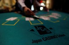 A logo of Japan casino school is seen as a dealer puts cards on a mock black jack casino table during a photo opportunity at an international tourism promotion symposium in Tokyo in this September 28, 2013 file photo.  REUTERS/Yuya Shino/Files