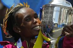 Kenya's Rita Jeptoo holds the trophy after winning the women's division at the 118th running of the Boston Marathon in Boston, Massachusetts April 21, 2014.     REUTERS/Brian Snyder