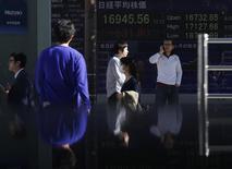 Una persona habla en su teléfono celular frente a una pantalla electrónica que muestra el índice Nikkei en Tokio, 04 noviembre, 2014.   Las bolsas de Asia retrocedían el miércoles en momentos en que los precios del petróleo ampliaban sus pérdidas tras unos débiles datos económicos de China, y el dólar se tomaba un respiro tras su repunte de esta semana. REUTERS/Yuya Shino