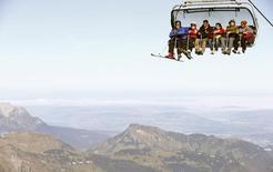 Туристы на подъемнике близ Энгельберга, Швейцария 19 октября 2013 года. Резкое сокращение числа гостей из РФ перед предстоящим зимним сезоном вызывает сильное беспокойство у работников туриндустрии на альпийских горнолыжных курортах, которые в прежние годы привыкли хорошо зарабатывать на щедрых российских туристах. REUTERS/Arnd Wiegmann