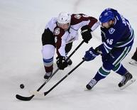 Colorado Avalanche defenseman Erik Johnson (6) reaches for the puck against Vancouver Canucks forward Nicklas Jensen (46) during the third period at Rogers Arena. The Colorado Avalanche won 4-2. Mandatory Credit: Anne-Marie Sorvin-USA TODAY Sports