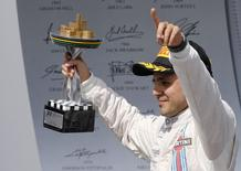 Third placed Williams Formula One driver Felipe Massa of Brazil lifts the trophy during podium ceremony after the Brazilian Grand Prix in Sao Paulo November 9, 2014. REUTERS/Paulo Whitaker